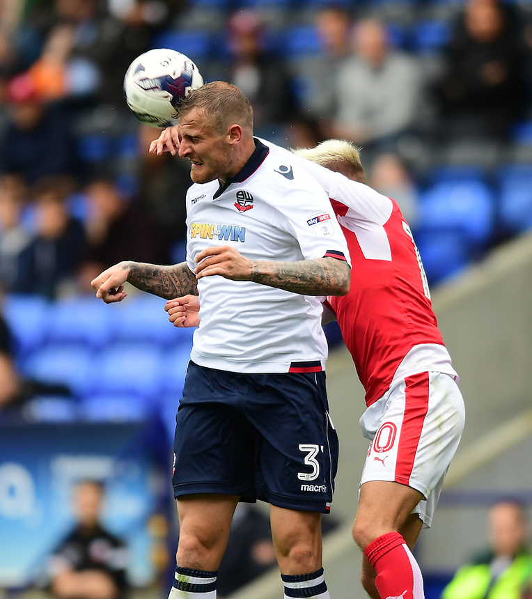Bolton Wanderers's David Wheater heads clear under pressure from Fleetwood Town's David Ball<br /> <br /> Photographer Chris Vaughan/CameraSport<br /> <br /> Football - The EFL Sky Bet League One - Bolton Wanderers v Fleetwood Town - Saturday 20 August 2016 - Macron Stadium - Bolton<br /> <br /> World Copyright &copy; 2016 CameraSport. All rights reserved. 43 Linden Ave. Countesthorpe. Leicester. England. LE8 5PG - Tel: +44 (0) 116 277 4147 - admin@camerasport.com - www.camerasport.com