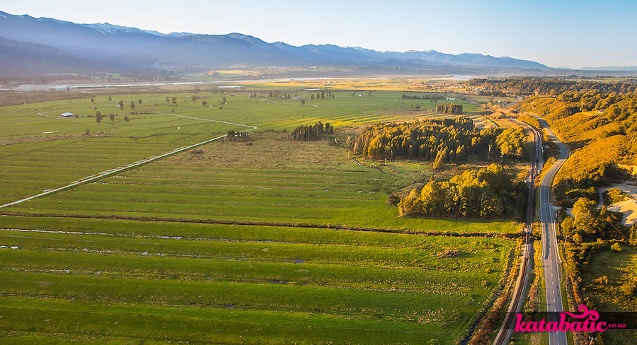 The humps and hollows of a Grey Valley dairy farm, State Highway 7, and the Midland Line catch the sun as it sets over the Paparoa Range.