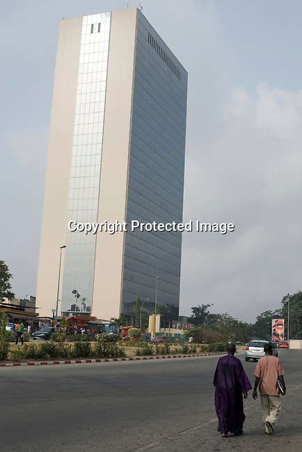 People walk past the provisional headquarters of the African Development Bank in Abidjan, Ivory Coast. The Bank moved to Tunisia over 10 years ago due to political instability in the Ivory Coast.  It returned the operations of the Bank to Abidjan in 2014.