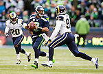 Seattle Seattle Seahawks Russell Wilson (3) scrambles away from St. Louis Rams defensive end Robert Quinn (94) and cornerback Lamarcus Joyner  (20) after passing during the second quarter  at CenturyLink Field in Seattle, Washington on December 28, 2014. The Seahawks officially wrapped up the No. 1 seed in the NFC playoffs shortly after beating the Rams, 20-6. Despite the Cowboys and Packers also winning to finish 12-4, the Seahawks (12-4) won the multi-team tiebreaker and earned home-field advantage throughout the playoffs for the second consecutive season.  ©2014. Jim Bryant Photo. All Rights Reserved.