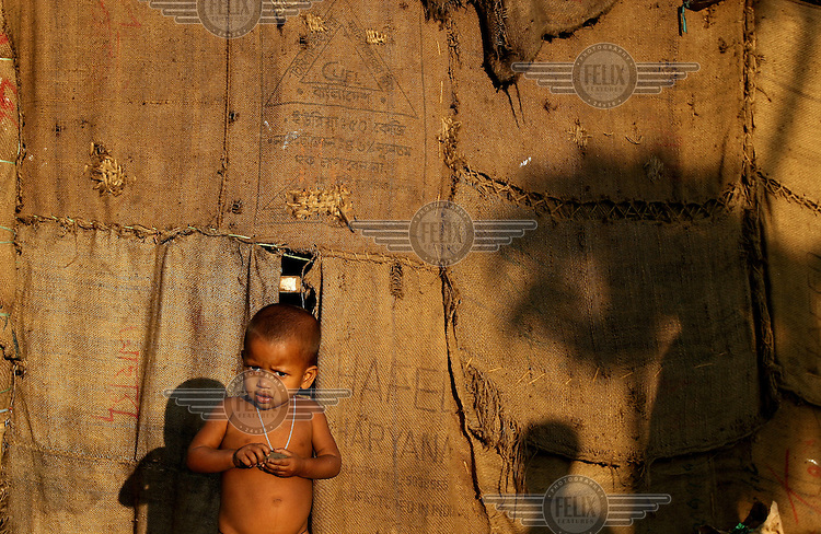 A naked child stands outside a slum dwelling made of hessian sacks.