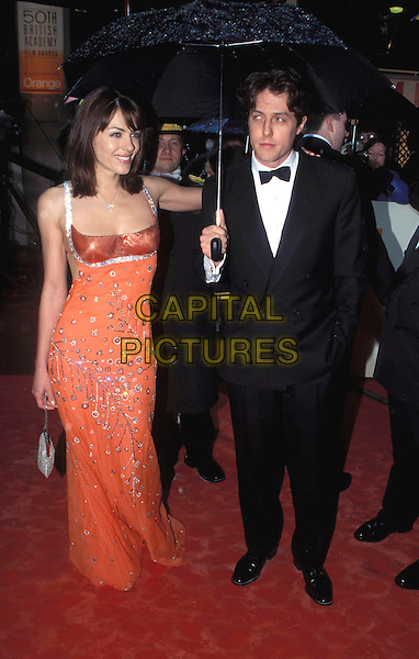 LIZ HURLEY & HUGH GRANT..50th BAFTA Awards 1998..Ref: 7314 ..orange dress, umbrella, full length, small handbag..www.capitalpictures.com..sales@capitalpictures.com