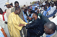 Senegal. Thiaroye sur Mer. 15 km from Dakar. Youssou Ndour. The famous worldmusic artist makes music greets man wearing a yellow traditional dress (boubou) in a open air and public gathering. Youssou Ndour has been invited by the population of  Thiaroye sur Mer to receive an award for his leading role in bringing african music (senegalese) to the world. He is recognised by the crowd as a true african musician and artist. © 2000 Didier Ruef