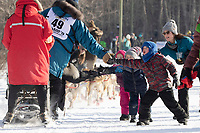 Youngster Kyde Friesen and family members give a high-five to musher Ryan Santiago during the ceremonial start of the 2019 Iditarod in midtown Anchorage, Alaska on Saturday March 2.<br /> <br /> Photo by Jeff Schultz/  (C) 2019  ALL RIGHTS RESERVED