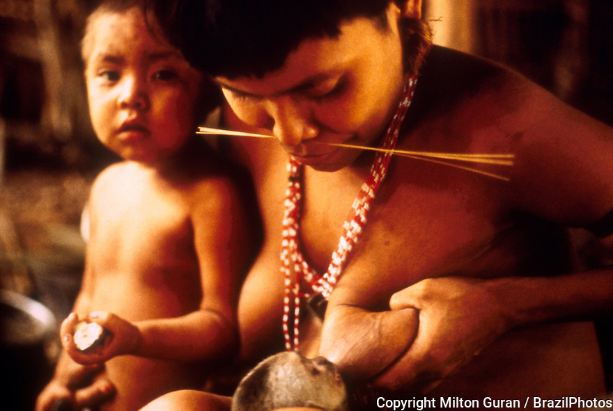 Yanomami indigenous people. Woman breast-feeds young monkey. Amazon rain forest, state: Roraima, Brazil.