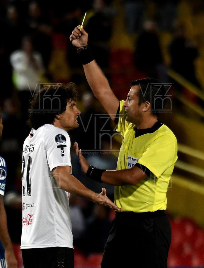 BOGOTÁ - COLOMBIA, 15-08-2018: Julio Bascuñán (Der.) árbitro Chileno, muestra tarjeta amarilla a Blas Cáceres (Izq.) jugador de General Díaz (PAR), durante partido de vuelta entre Millonarios (COL) y General Díaz (PAR), de la segunda fase por la Copa Conmebol Sudamericana 2018, en el estadio Nemesio Camacho El Campin, de la ciudad de Bogotá. / Julio Bascuñán, Chilean referee, shows yellow card to Blas Caceres (L) player of General Diaz (PAR), during a match of the second leg between Millonarios (COL) and General Diaz (PAR), of the second phase for the Conmebol Sudamericana Cup 2018 in the Nemesio Camacho El Campin stadium in Bogota city. VizzorImage / Luis Ramirez / Staff.