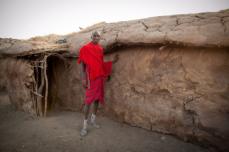 "Masai dwellings are oval in shape, low roofed and have a skeleton structure made from branches pasted with fresh cow dung which bakes hard under the hot sun.  The structural framework is formed of timber poles fixed directly into the ground and interwoven with branches that are plastered with a mix of mud, sticks, grass, cow dung and human urine, and ash. Women do the entire job of building the huts and are also responsible for maintenance especially during wet weather when there may be leakage. One hut may take up to three weeks to complete.  Masai huts are very small with perhaps two ""rooms"" and not enough room for these tall Maasai to stand upright or lie fully stretched. They are also very dark with a small door-way and tiny hole in the roof that lets a little light in and releases smoke from the fires."