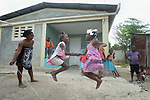 Children jump rope in front of a new house built by Servicio Social de las Iglesis Dominicanas in the Haitian community of Ganthier. SSID, a member of the ACT Alliance, has worked extensively in the community since it was devastated in 2016 by Hurricane Matthew, building new homes and helping residents create new livelihoods. <br /> <br /> Parental consent obtained.