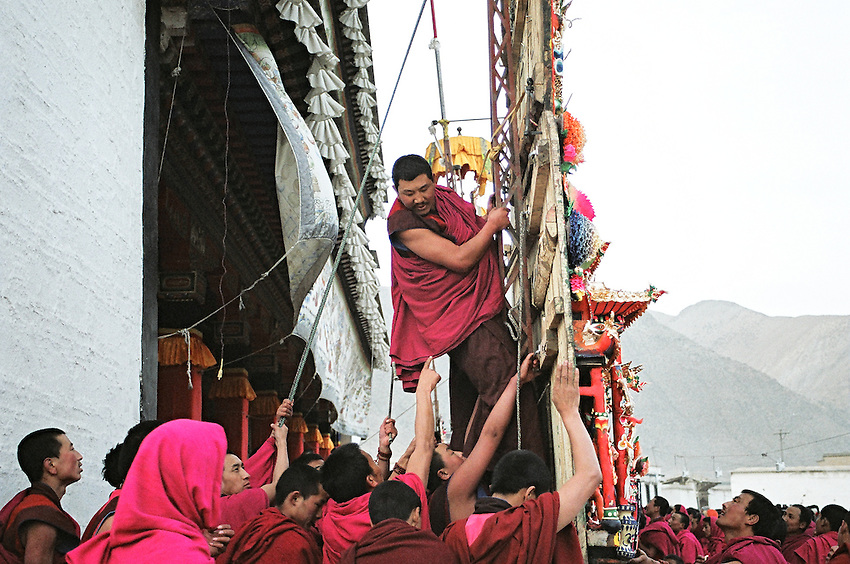 A monk from the Tantric college is  attaching one of the butter sculptures to a mast; the 3rd day of  Monlam Chenmo (the Great Prayer), in the monastery of Labrang (Yellow Hats). The sculptures made of yak butter and barley flour are only displayed at the end of the day to avoid the light of the sun, and pilgrims will come to see them and to pray deities until late in the night. Xiahe, China, 03/04/2007.