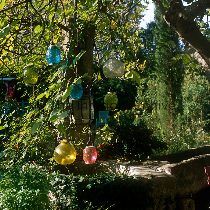Coloured glass lanterns hang from the branches of a tree in a garden.