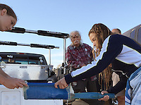 San Diego CA, USA.  7th, December 2015:  Don Gross (C) looks on as Mission Bay High School Seniors Alina Snyder (L) and Peral Moore use a wand to check a chip embeded in the cheek of a juvenile white sea bass before releasing it into Mission Bay.  The school is one of the first schools in the state to participate in the Seabass in the Classroom Project, which is a collaboration between Hubbs-Sea World Research Institute and the California Department of Fish and Game.