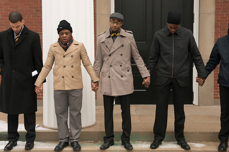 (left to right) Jordan Tyner, Derrick Holifield, Brandon Chestnut and Jerry Mobley of the Alpha Phi Alpha Fraternity hold hands as Chestnut opens the Silent March with prayer on Martin Luther King Day. (Photo by Olivia Wallace)
