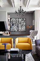 The focus of the contemporary living room is a matching pair of yellow leather armchairs, a striking contrast to the grey and white decorative palette