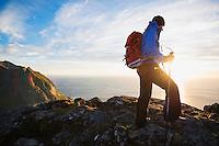 Female hiker hiking in Evening summer sun on summit of Ryten, Moskenesoy, Lofoten Islands, Norway