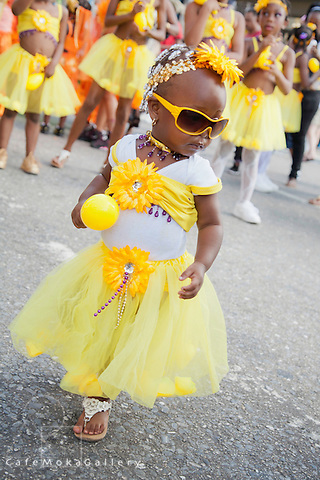 """Junior Carnival - Toddler playing mas in yellow skirt and flowers with maracas """"Culture Shock"""",""""Friends of Genesis"""""""