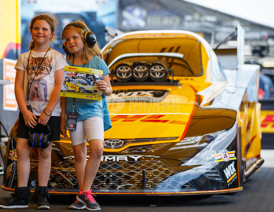 Apr 22, 2017; Baytown, TX, USA; Two young girls pose for a photo in front of the car of NHRA funny car driver J.R. Todd during qualifying for the Springnationals at Royal Purple Raceway. Mandatory Credit: Mark J. Rebilas-USA TODAY Sports