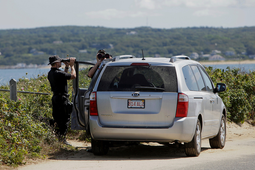 Secret Service agents watch as U.S. President Barack Obama rides bikes with family and friends along Lobsterville Beach in Aquinnah on Martha's Vineyard...Photo by Brooks Kraft/Corbis..