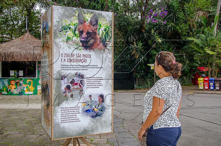 Mulher lendo placa na Fundação Parque Zoológico de São Paulo, São Paulo - SP, 02/2016. Uso de imagem autorizado.
