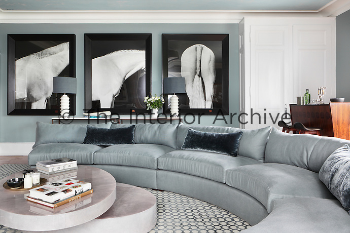 A tryptic of black and white photographs of horses creates a striking feature on one wall of the blue-grey living room