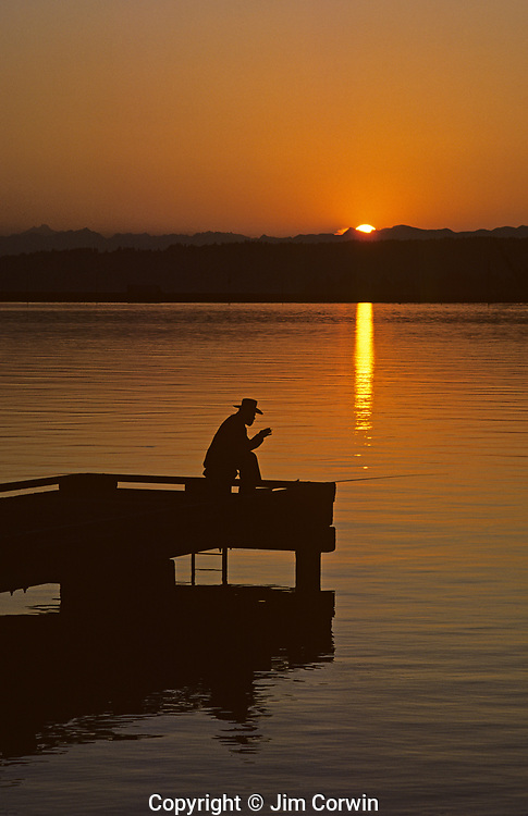 Sunrise with older man silhouetted fishing off dock on lake Washington with Cascade Mountains Seattle Washington State USA