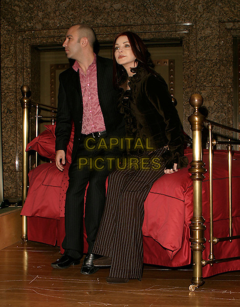 BRUNO SCHIAVI & PRISCILLA PRESLEY.Press launch & photocall, Bed Linen department (2nd floor), Harrods, London, UK..April 5th, 2006.Ref: AH.full length brown ruffles black pinstripe trousers sitting bed.www.capitalpictures.com.sales@capitalpictures.com.© Capital Pictures.