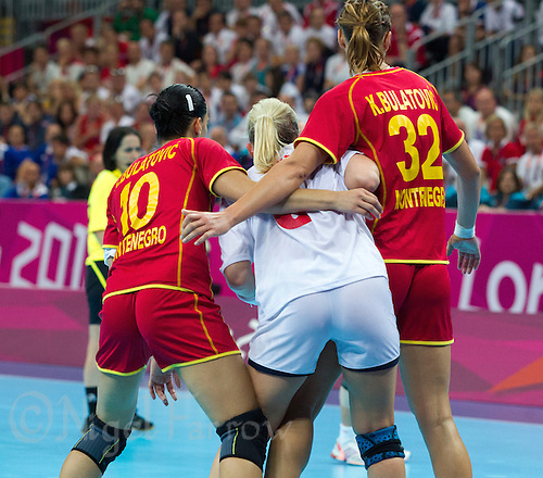 11 AUG 2012 - LONDON, GBR - Andjela Bulatovic (MNE) (left) and Katarina Bulatovic (MNE) (right) of Montenegro blocks Heidi Løke (NOR) (centre) of Norway's path to goal during the women's London 2012 Olympic Games handball final at the Basketball Arena in the Olympic Park, in Stratford, London, Great Britain .(PHOTO (C) 2012 NIGEL FARROW)