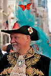 A man in the New York City Easter Parade wearing an embroidered coat and a black hat with a blue netting with orange butterflies in it