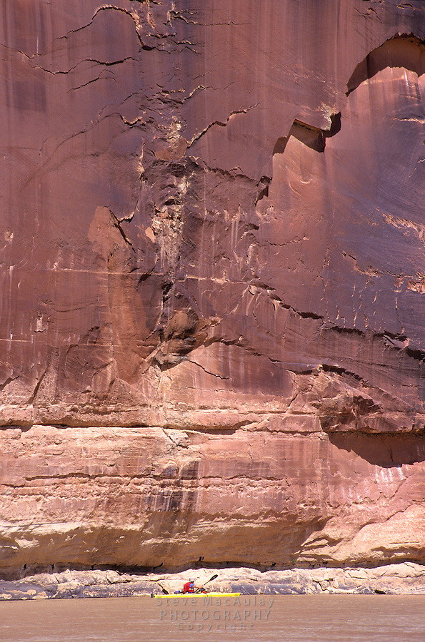 Solitary paddler dwarfed by towering sandtone cliff rising from the river, kayaking on the Green River, Canyonlands National park, Utah