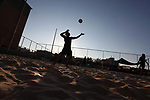 Palestinian players compete in a beach volleyball match during a local competition, in Gaza city on June 15, 2019. Photo by Mahmoud Ajjour