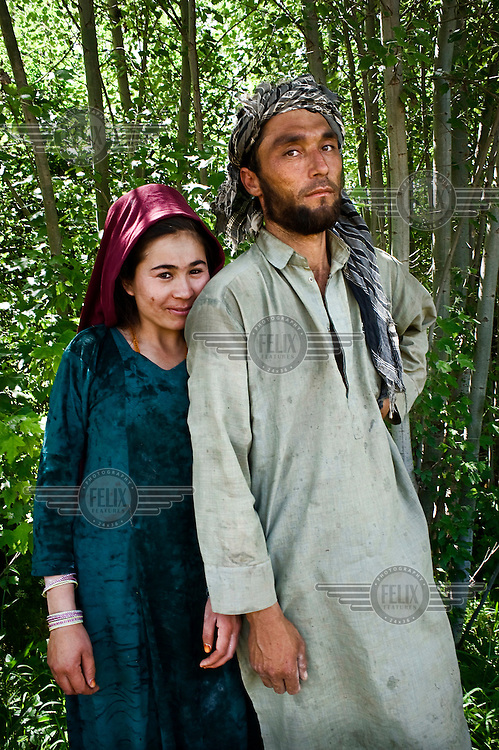 A husband and wife stand together in a glade of trees.