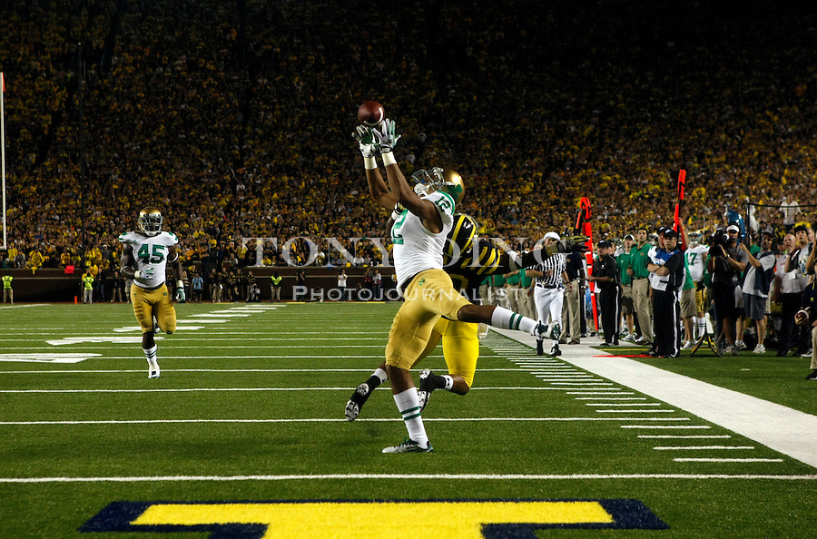 Notre Dame cornerback Robert Blanton (12) intercepts a Denard Robinson pass intended for Michigan wide receiver Jeremy Gallon (10) in the fourth quarter of an NCAA college football game, Saturday, Sept. 10, 2011, in Ann Arbor. Michigan won 35-31. (AP Photo/Tony Ding)