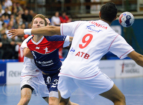 06 APR 2012 - LONDON, GBR - Great Britain's Ciaran Williams (GBR) (left, in blue and red) passes during the men's 2012 London Cup match against Tunisia at the National Sports Centre in Crystal Palace, Great Britain (PHOTO (C) 2012 NIGEL FARROW)