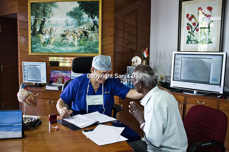 58 year old heart surgeon, Dr. Devi Prasad Shetty speaks with a patient during OPD in his office at the Narayana Hrudayalaya in Bangalore, Karnataka, India. Photo: Sanjit Das/Panos