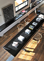 A view from above of a long black table and light wood chairs. A low built-in cabinet runs along the length of one wall.