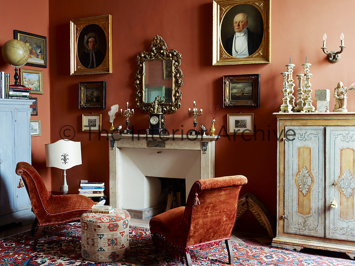 The 19th century slipper chairs retain their original velvet, the colour matching perfectly the terracotta of the study walls