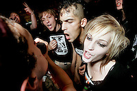 Concert-goers join in with the band during a punk concert in the basement of the White House in Woodstock, Illinois.  The White House was a small suburban residential home rented by a group of 20-somethings in Woodstock, Illinois, a distant northwestern suburb of Chicago.  For about a year, the renters of the house staged punk-rock concerts in the house's small basement, without the approval of the neighborhood, local government, or police.  .