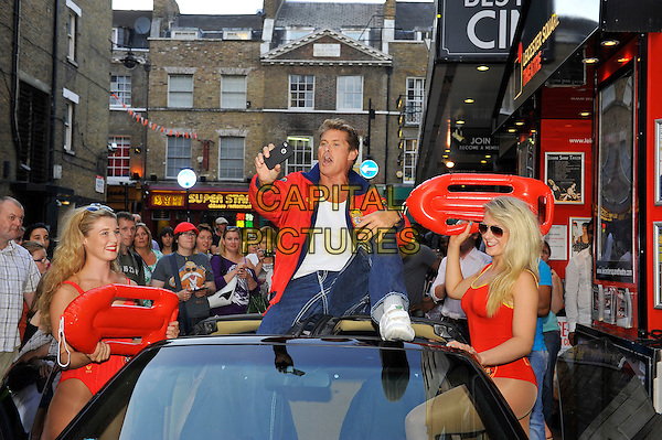 David Hasselhoff .photocall at Leicester Square Theatre, Leicester Square, London, England, UK,.17th August 2012..full length baywatch red jacket girls floats swimsuits black car jeans white trainers car roof sitting on top of taking photo iphone .CAP/MAR.© Martin Harris/Capital Pictures.