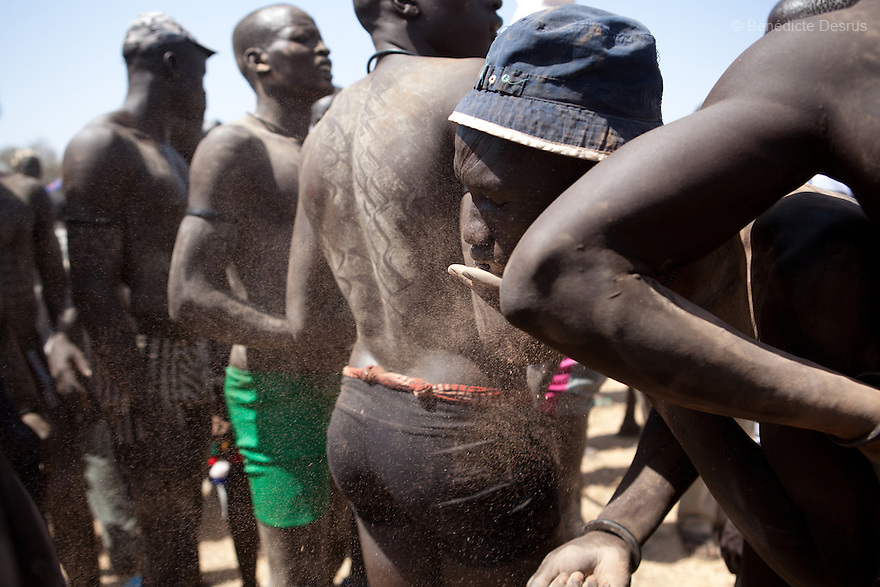 18 december 2010 - Juba, Southern Sudan - Wrestlers of the Mundari tribe from Central Equatoria State apply dried cattle dung before the final of South Sudan's first commercial wrestling league between their tribe and the Dinka wrestlers from Bor, Jonglei State at Juba Stadium. The matches attracted large numbers of spectators who sang, played drums and danced in support of their favorite wrestlers. The match organizers hoped that the traditional sport would bring together South Sudan's many different tribes. Photo credit: Benedicte Desrus