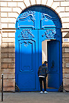 A boy peaks into a large blue doorway in the historic district of Le Marais in Paris, France