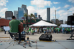 Lonely acoustic guitarist sings cover songs to a growing Saint Patrick's Day crowd at Lucky's Bar and Grill in downtown Houston, Texas.