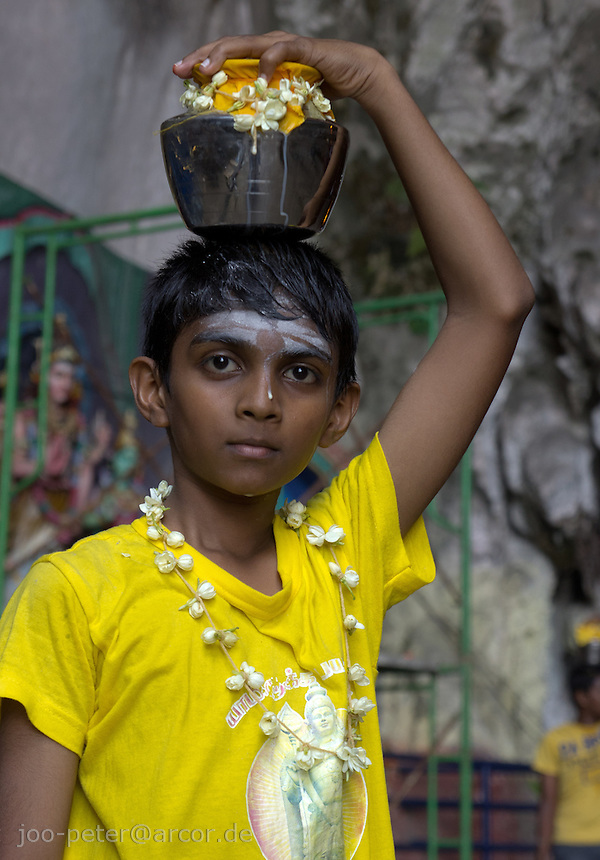 boy carrying metal pot with holy milk while Thaipusam ceremonies inside Batu Caves, Kuala Lumpur, Malaysia, 2012. . Thaipusam ceremonies, celebrated by tamile Hindu community in Malaysia, take place  in Sanctuary of Batu Caves at the border of Kuala Lumpur, each year around end of January or beginning of February, according to Hindu moon calendar. The event is paying hommage to Lord Murugan, a spirit or god created by Shiva to lead the army of gods against the army of evil demons, finally defeating the evil spirits. There are many ways to present offerings or sacrifices for this major religious event. Devotees mortify their bodies by carrying heavy kavaris with spears fixed in their skin or fruits, flowers and little post with holy milk fixed with hooks in their skin, ascending the stairways to the sanctuary in trance, `followed by assistant  taking care and musicians playing loud and fast rhythmic trance music.  Many families shave their head in a ritual before ascending the stairways, as part of rituals to obtain salvation for their ancestors.