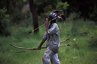 Guarani-Kaiowas indigenous people - acculturated brazilian indian smokes cigarette - mix of traditional culture ( native weapons - bow and arrows, head adornment, body painting ) and influence of the white culture - clothes, jeans, cigarette. Mato Grosso do Sul State, mid-west Brazil.