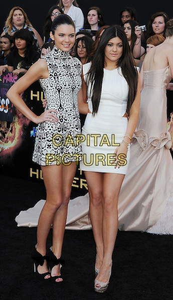 "Kendall Jenner and Kylie Jenner.The World Premiere of ""The Hunger Games"" at Nokia Theatre in Los Angeles, California at LA Live, USA..March 12th, 2012.full length black white print sleeveless dress sisters siblings family.CAP/ROT/TM.©Tony Michaels/Roth Stock/Capital Pictures"
