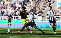 Pictured L-R: Wilfried Bony of Swansea gets past Cheik Tiote of Newcastle. Saturday 19 April 2014<br />