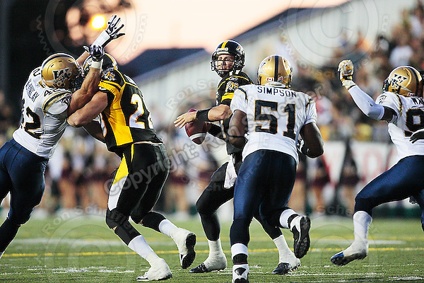 Aug 3, 2007; Hamilton, ON, CAN; Hamilton Tiger-Cats quarterback (11) Jason Maas looks for an open receiver while under pressure from Winnipeg Blue Bombers linebacker (51) Barrin Simpson during the first half at Ivor Wynne Stadium. Mandatory Credit: Ron Scheffler