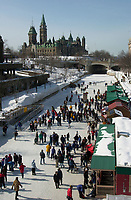 Ottawa, February 24, 2001.Families and week enders skate on the Rideau Canal in downtown Ottawa, CANADA, february 24,2001..We recognize the Parliement Tower as well as  a Canadian Governement Buiding in the background.Photo by Pierre Roussel, 2001.NOTE : RAW TIFF from Nikon D-1