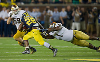 Wolverines running back Fitzgerald Toussaint (28) carries the ball as Notre Dame Fighting Irish nose tackle Louis Nix (1) and linebacker Jarrett Grace (59) defend in the third quarter