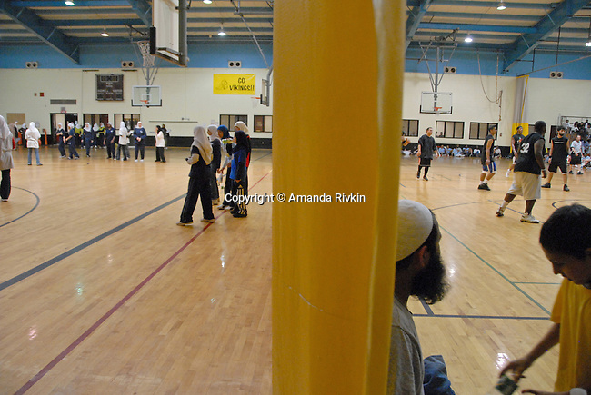 Women and men share the gymnasium during the basketball tournament at the Islamic Games in South Brunswick, New Jersey on May 26, 2007.   Events are passed the schedule so men are restricted to their half of the gymnasium.