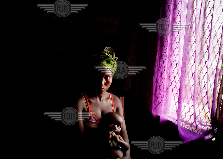 A mother and her child wait to see a doctor in a PHU (primary health unit) near Bo.