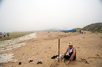 A man sits on the beach near piles of dead algae on the Shilaoren Beach in Qingdao, Shandong, China. The bay is covered by a massive algal bloom and threatens events in the 2008 Olympics...Qingdao is the host of the sailing events for the 2008 Summer Olympics. Algae blooms like this have become common in inland lakes in China, often caused by high pollution in bodies of water.  The city is asking for help and forcing residents to take part in the cleanup effort before the Olympic events..